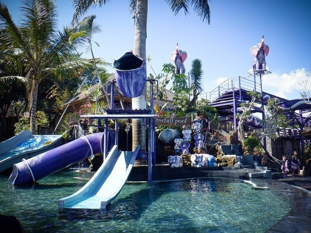 Slides and a giant splash bucket at a pool at Toya Devasya Bali hot springs.