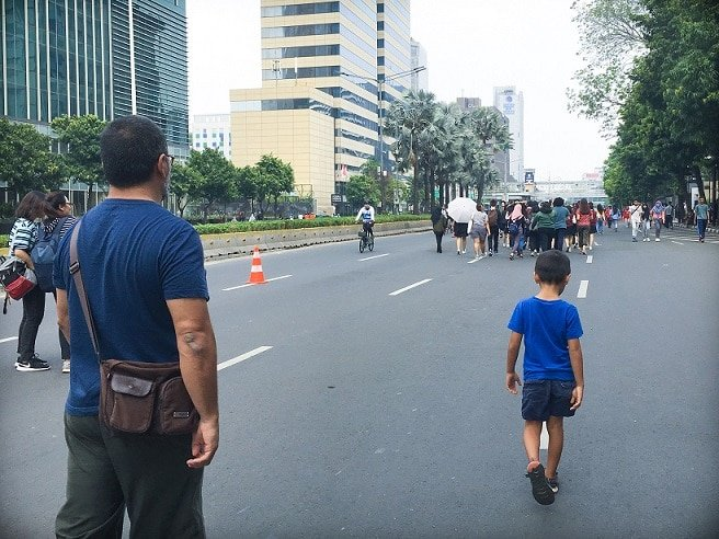 A man and boy walking through the streets of Jakarta while traveling with kids in Indonesia
