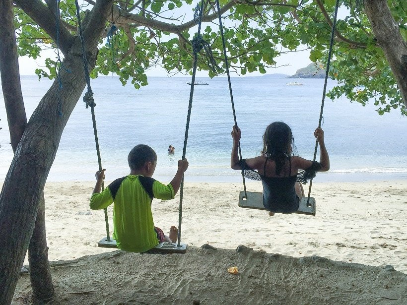 Children from traveling families of color swinging on tree swings on the beach, looking out at water