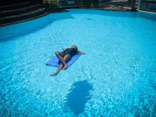 A girl floating in a pool at a luxury resort in Lombok, Indonesia, taking advantage of resort day passes.
