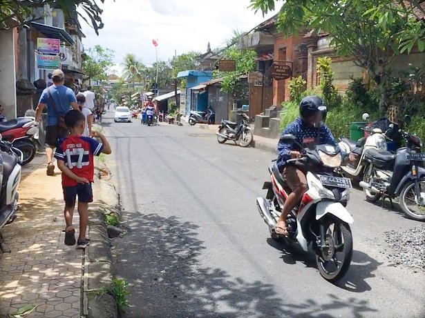 A side street in Ubud where you can do a scooter rental in Bali, with a scooters parked on the side of the road, and a person on a scooter driving on the road.