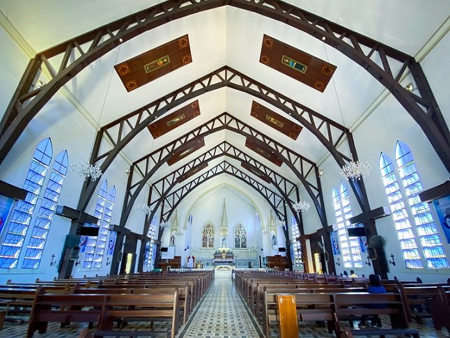 Interior of the Immaculate Conception Cathedral in Puerto Princesa, Philippines. The altar is in the background, in the center is the aisle, with pews on either side of the aisle