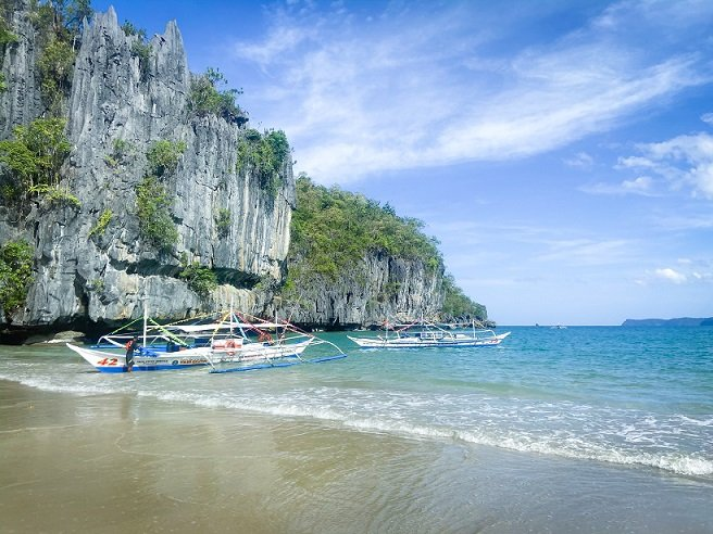 Boats on the beach near the Underground River, a stop during a Puerto Princesa itinerary in the Philippines
