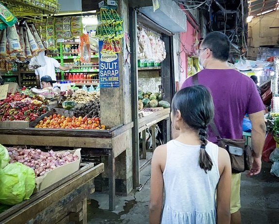 A man and a girl walk through the Old Public Market in Puerto Princesa, Philippines, passing by produce stalls selling cabbage, shallots, tomatoes and chiles, as part of a Puerto Princesa itinerary