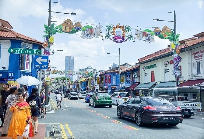Pedestrians and cars along Serangoon Road in Little India, one of the places to visit for things to do in Singapore on a budget