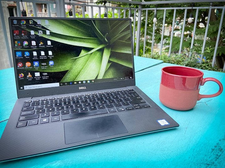 A laptop and cup on a blue table on a rooftop deck, part of an Airbnb property that families can book for Airbnb family travel