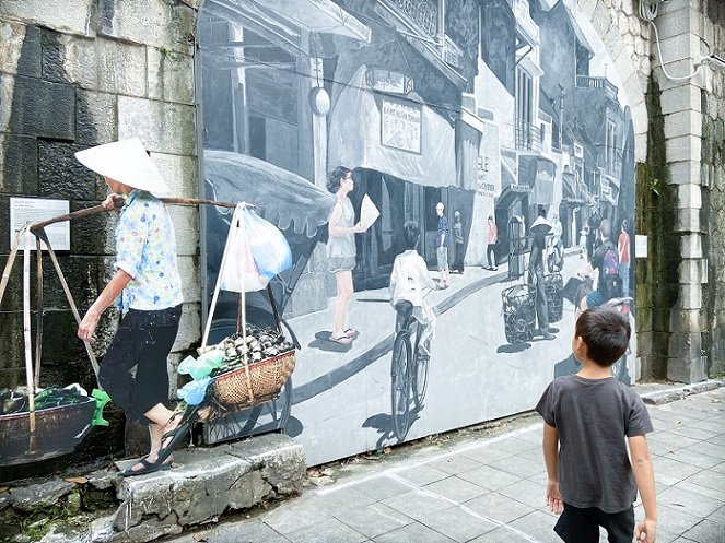 A child walking by a mural in Hanoi, Vietnam while doing long term family travel