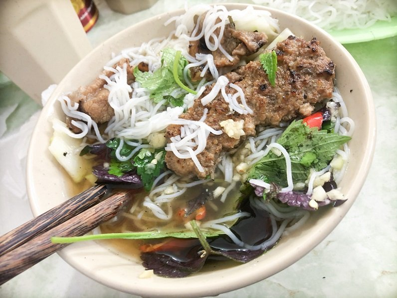 A bowl of bun cha mixed with vermicelli noodles and vegetables, a popular food in Hanoi