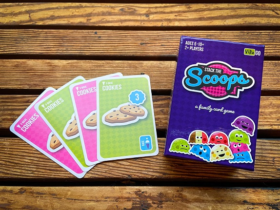 A set of playing cards and a box called Stack The Scoops on a wood background, used as family-friendly worldschooling resources