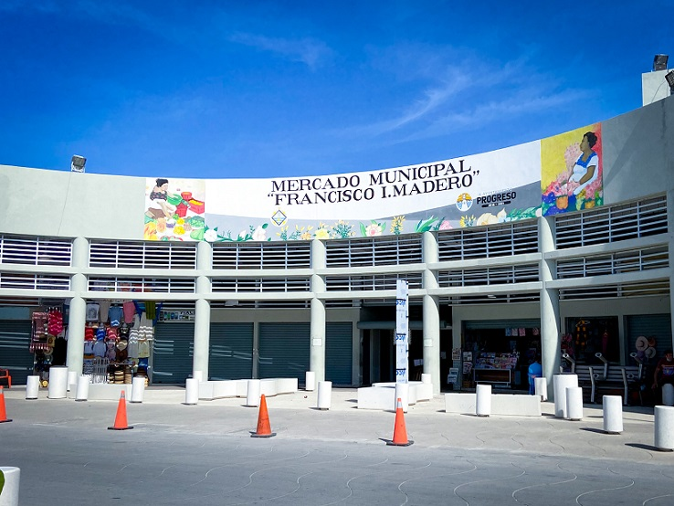 """The entrance to the Municipal Market, one of the things to do in Progreso. A curved building facade, with a sign on top saying, """"Mercado Municipal Francisco I.Madero"""". Small shops line the front of the building. Orange cones are in a line the front of the entrance to the building."""