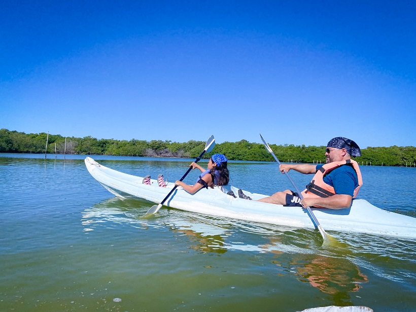 A young girl and a man kayaking in a double kayak with mangroves in the background