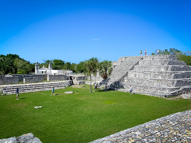 A stone pyramid with palm trees in front of it and next to a platform made of stone. A grassy field sits in front of the pyramid and stone platform. The pyramid is located in archaeological site, Xcambo, one of the things to do in Progreso, Mexico.