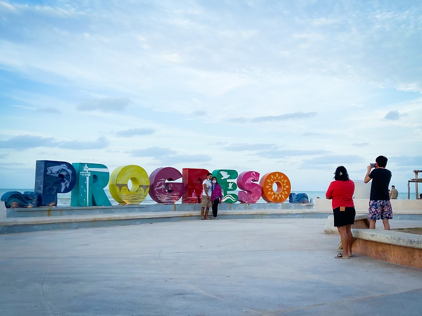 Man and woman posing in front of a Progreso letter sign, with the ocean in the background, exploring things to do in Progreso