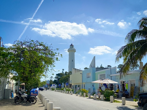 A scene of a Mexican street with a lighthouse in the background, one of the things to do in Progeso