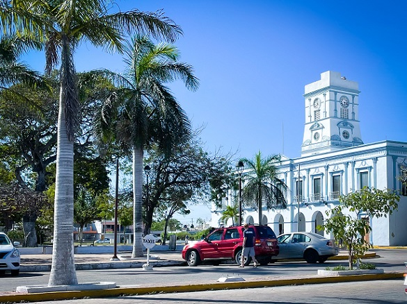 A blue and white colonial building in Progreso, Mexico with cars parked in front of it and palm trees next to it.