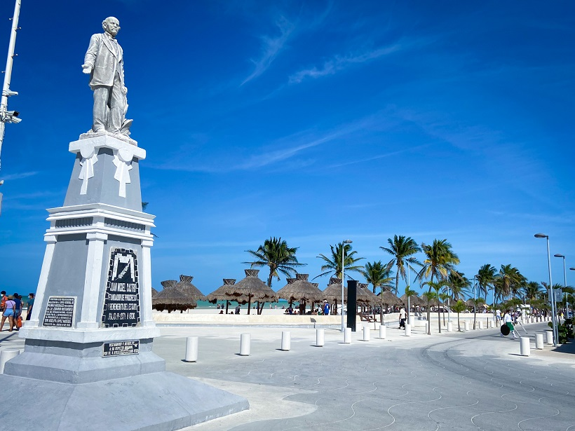 A statue with a street in the background lining a beach with palm trees and beach shades